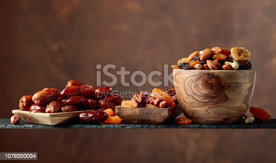 istock Various dried fruits and nuts in wooden dish. 1076550034
