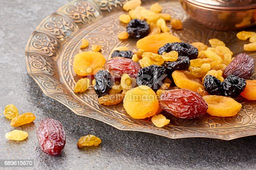 689618578 istock photo Various dried fruits on toreutic plate over stone background 689615670