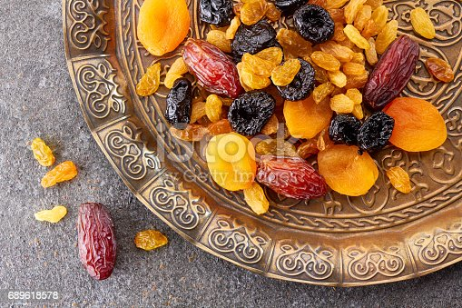 istock Various dried fruits on toreutic plate over stone background 689618578