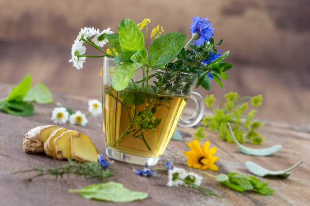various dried meadow herbs and herbal tea on old wooden table. fresh medicinal plants and in bundle. preparing medicinal plants for phytotherapy and health promotion - herbata ziołowa zdjęcia i obrazy z banku zdjęć