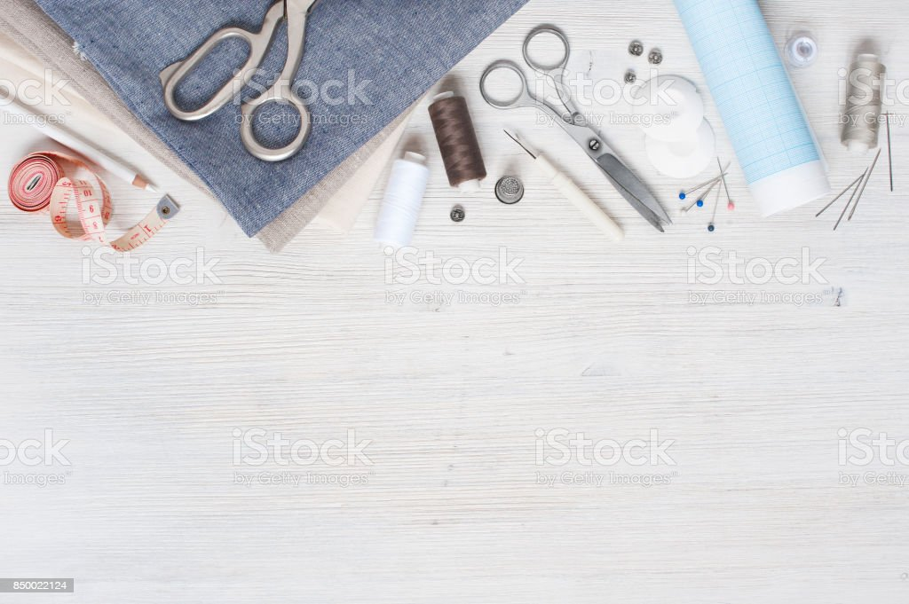Various fabric and sewing tools on the white wooden table stock photo
