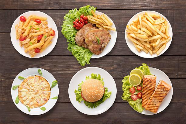 verschiedene speisen, die auf dem hölzernen hintergrund - hamburger makkaroni stock-fotos und bilder