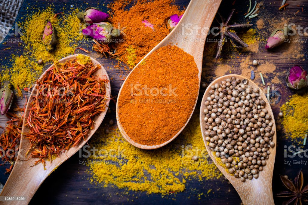 Colorful various spices and herbs in wood spoon on natural texture...