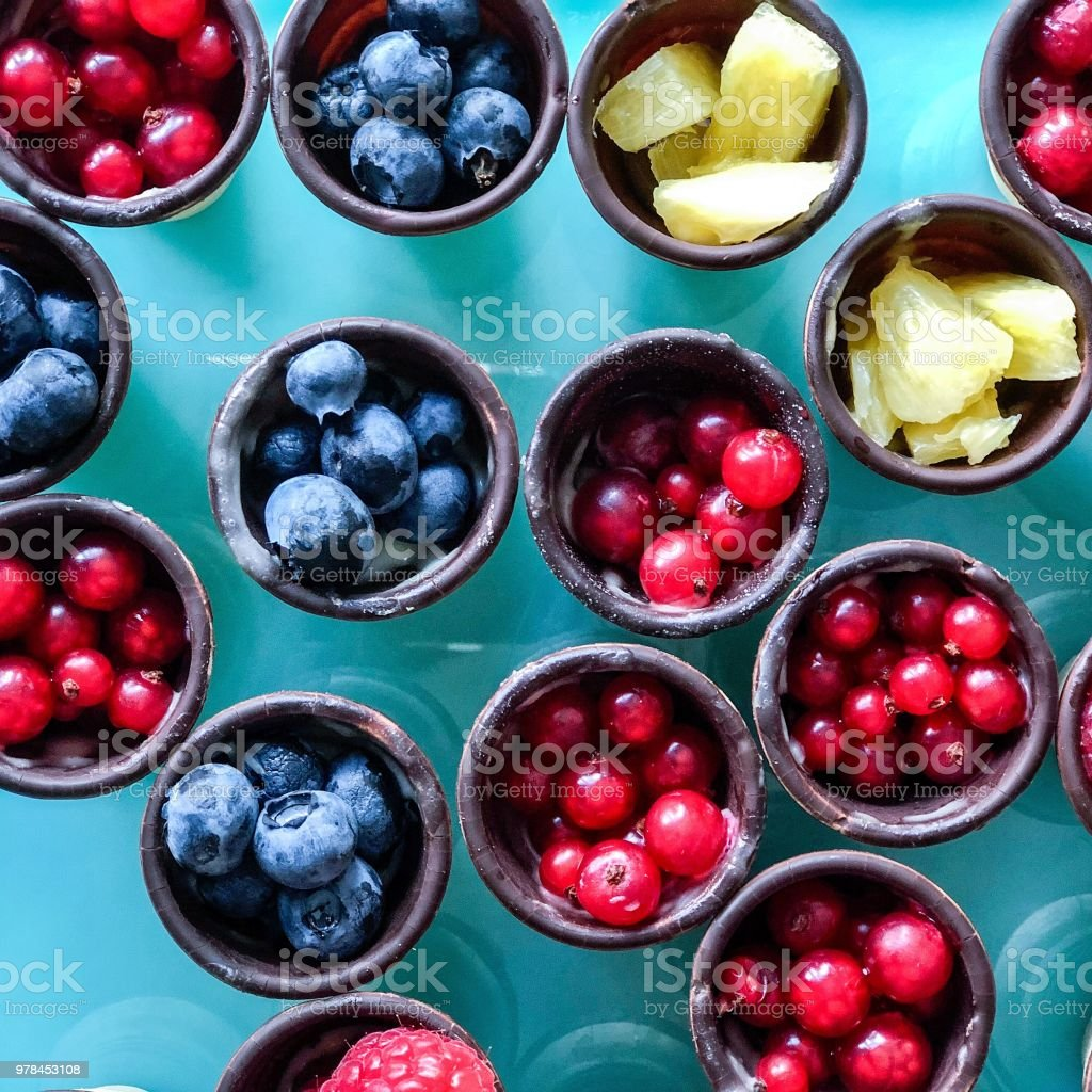 Various fresh fruits in chocolate cups stock photo