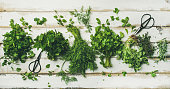 Flat-lay of bunches of various fresh green kitchen herbs. Parsley, mint, dill, cilantro, rosemary, thyme over white wooden background, top view. Spring or summer healthy vegan cooking concept