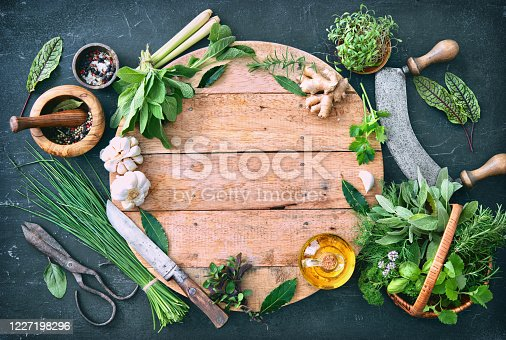 Various fresh herbs from garden with kitchen utensils on rustic table. Top view with copy space