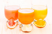 Various fresh juice in glass on wooden table. Healthy organic beverages with pieces of fruit. Vitamins background