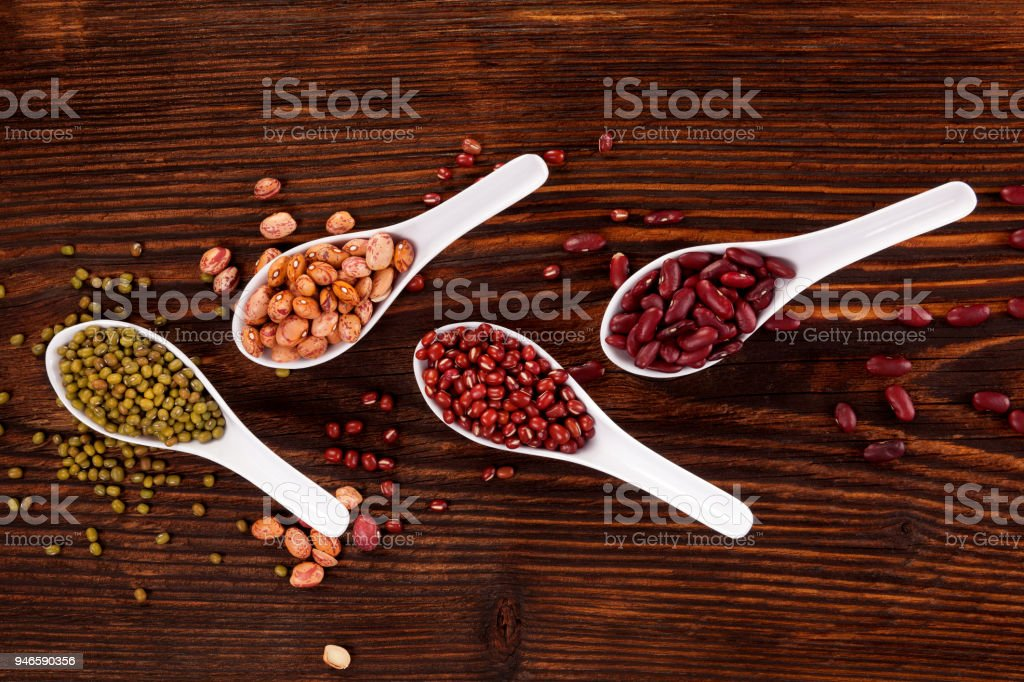 Various fresh legumes in spoons stock photo