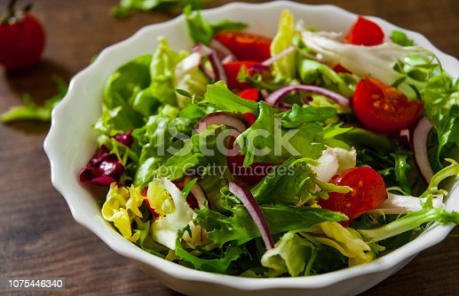 various fresh mix salad leaves with tomato in bowl on wooden background