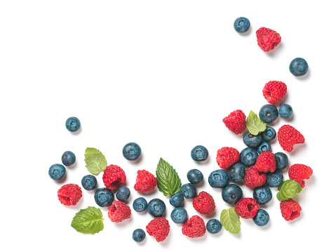Various fresh summer berries background with copy space for text.Creative layout of fresh blueberries, raspberries and mint leaves, isolated on white background with clipping path.Top view or flat lay