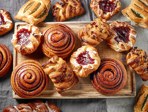 various freshly baked sweet buns various freshly baked sweet buns on wooden cutting board, top view sweet bun stock pictures, royalty-free photos & images
