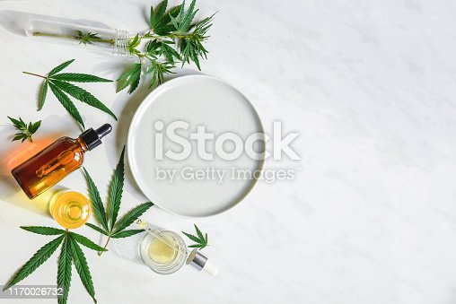 istock Various glass bottles with CBD oil, THC tincture and hemp leaves on a marble background. Copy space, mockup. Cosmetics CBD oil. 1170026732