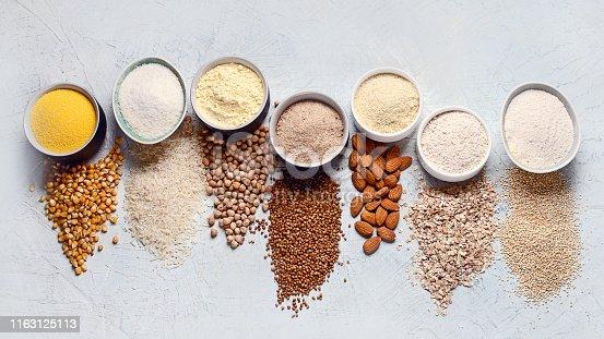 Various gluten free flour - chickpeas, rice, buckwheat, quinoa, almond, corn, oatmeal on grey background.