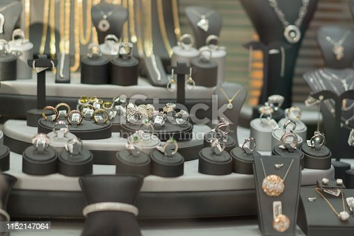 Various Golden rings with precious gems in jewelry shop, window close-up.
