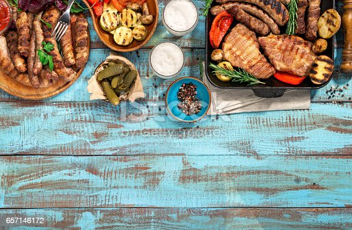 657146780 istock photo Various grilled food  on blue wooden table with copy space, grilled steak, grilled sausage, grilled vegetables and lager beer 657146172