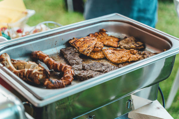 Various grilled meats (pork, chicken, beef) at a garden party in the evening stock photo