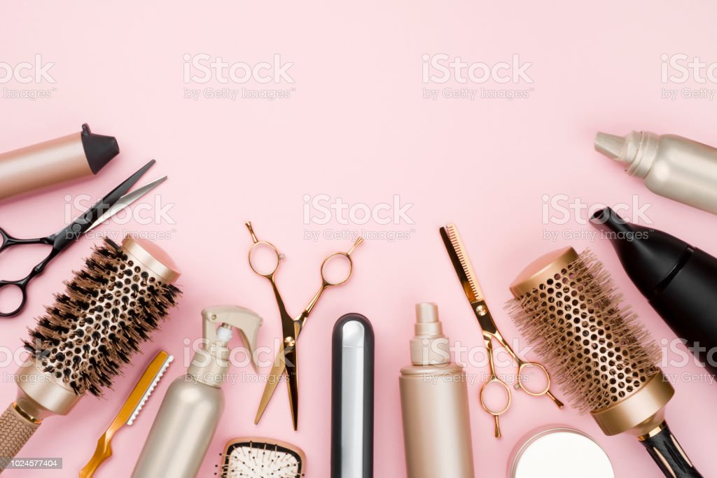 Various hair dresser tools on pink background with copy space stock photo