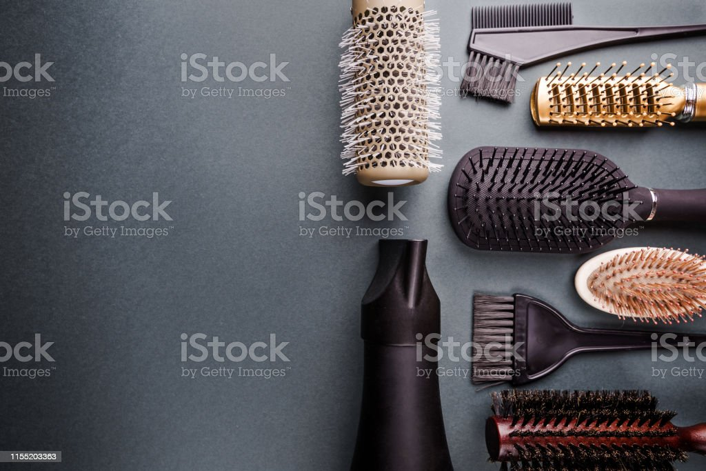 Various hair dresser tools on black background with copy space