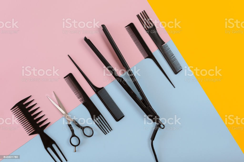 Various hair styling devices on the color blue, yellow, pink paper background, top view stock photo