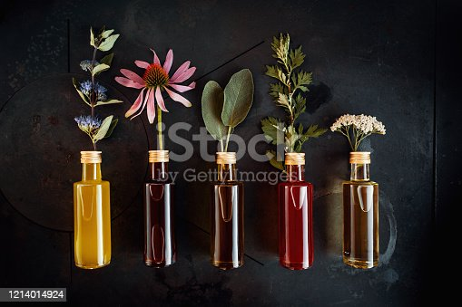 Various herbal oils with flowers decorated on a dark background