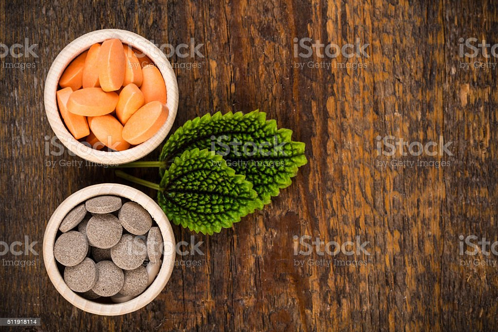 Various homeopathic medicine with green leaves stock photo