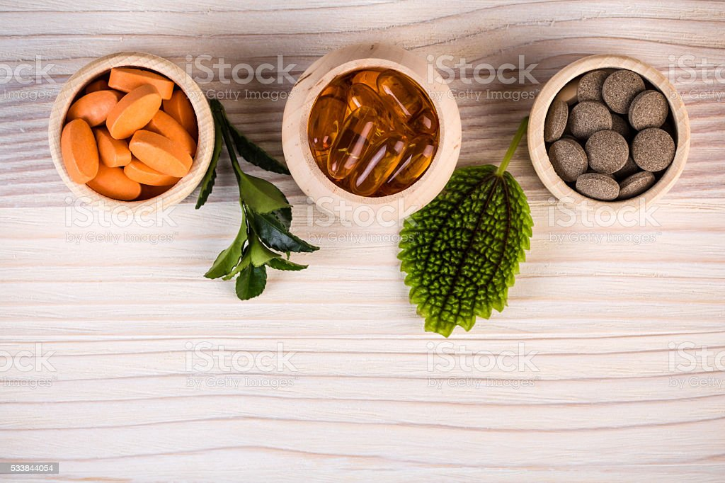 Various homeopathic pills and green leaves stock photo