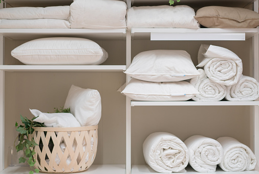Various household items such as pillows and quilts standing in the white cupboard.