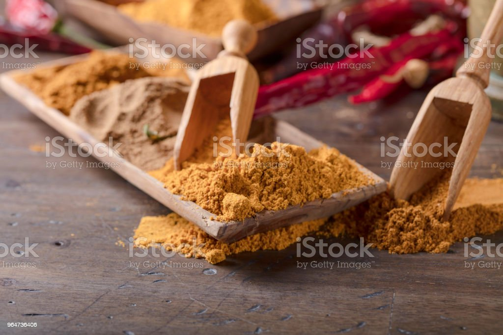 Various Indian spices with wooden spoons on a wooden table. royalty-free stock photo