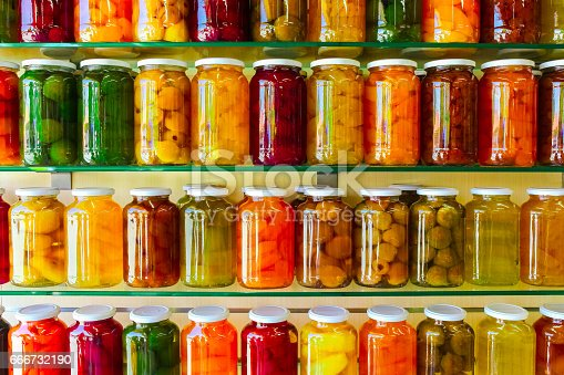 istock Various jars with Home Canning Fruits and Vegetables jam on glass shelves 666732190