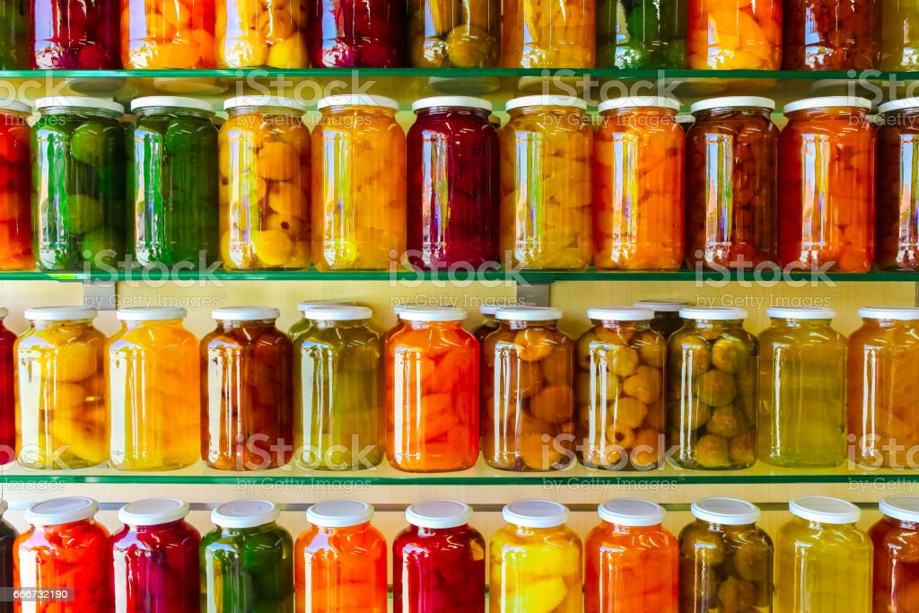 Various jars with Home Canning Fruits and Vegetables jam on glass shelves stock photo