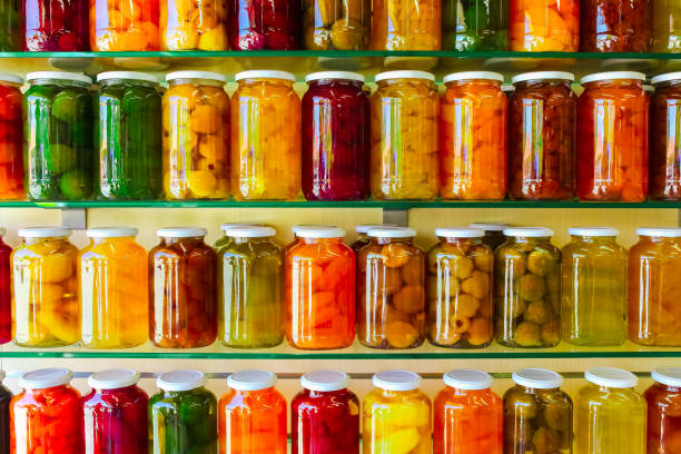 various jars with home canning fruits and vegetables jam on glass shelves - tomato can stock photos and pictures