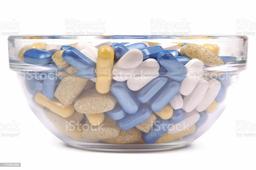 Various kind of pills in transparent cup. Isolated on white royalty-free stock photo