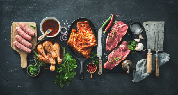 Various kinds of grill and bbq meats with vintage kitchen and butcher utensils stock photo