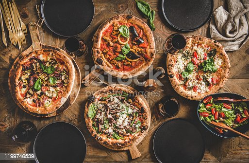 Pizza party dinner. Flat-lay of various kinds of Italian pizza, fresh salad and red wine in glasses over rustic wooden table, top view. Fast food lunch, celebration, gathering concept