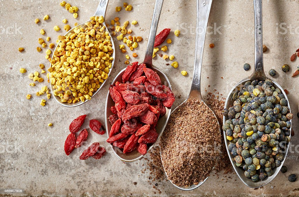 Various kinds of superfoods on tan background stock photo