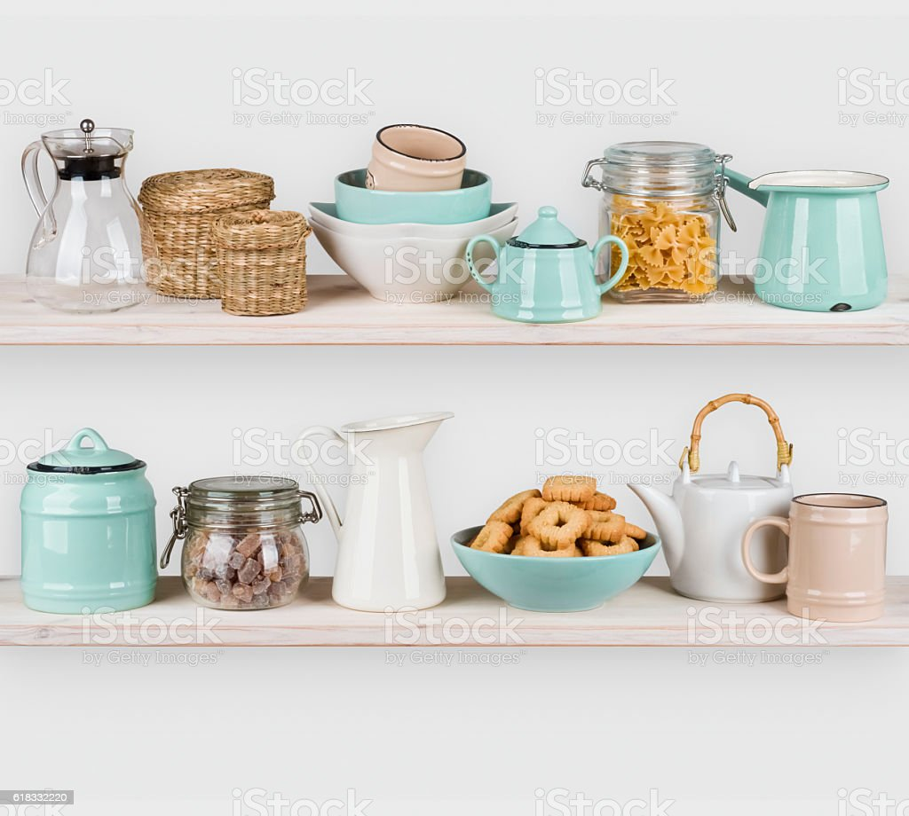 Various kitchen utensils and food ingredients isolated on wooden shelves stock photo