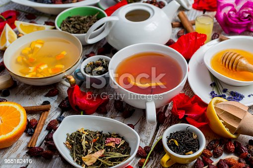 Various leaves of tea and spices on wooden background