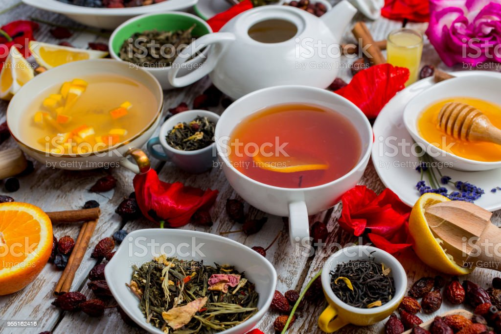 Various leaves of tea and spices on wooden background stock photo