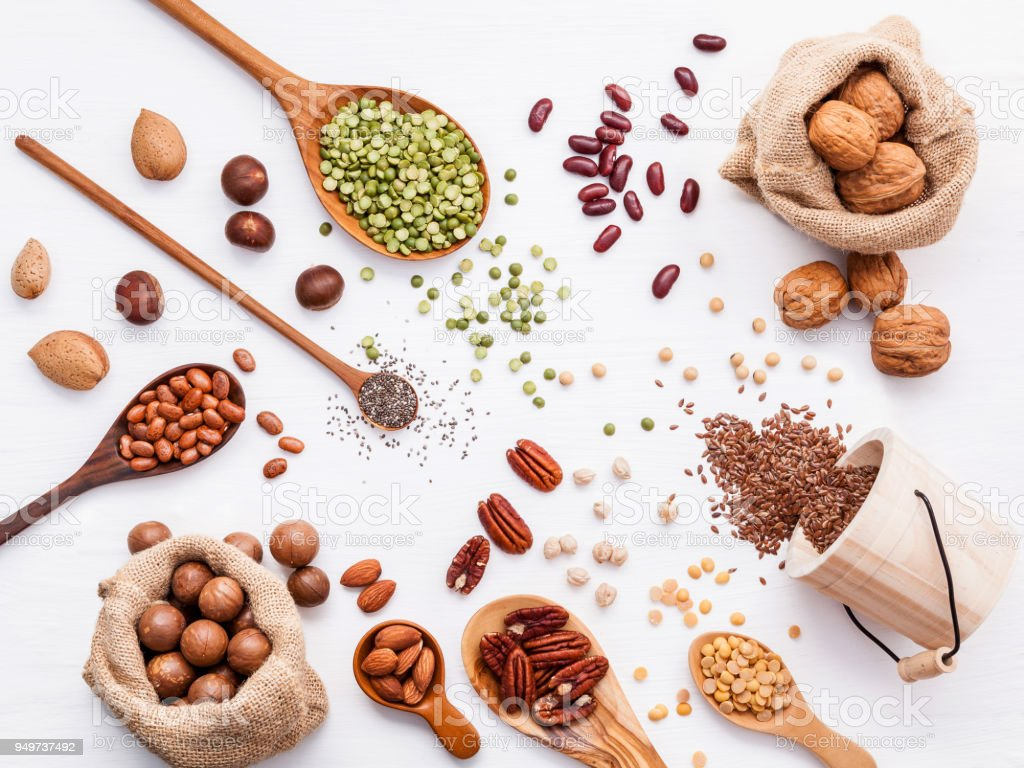 Various legumes and different kinds of nuts walnuts kernels ,hazelnuts, almond kernels,brown pinto ,soy beans ,flax seeds ,chia ,red kidney beans and pecan set up on white wooden table. stock photo