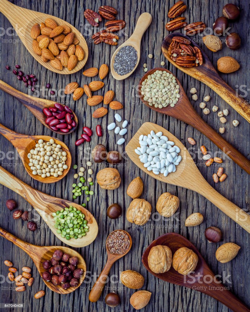 Various legumes and different kinds of nutshells in spoons. Walnuts kernels ,hazelnuts, almond ,brown pinto ,soy beans ,flax seeds ,chia ,chickpea ,red kidney beans and pecan on shabby wooden table. stock photo