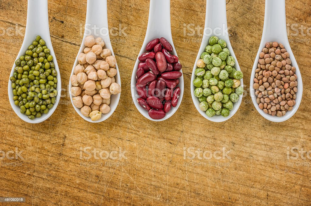 Various legumes on porcelain spoons stock photo