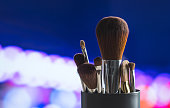 Various make up brushes in container on table with abstract bokeh ball background. Professional powder blending set with blurred city lights. Banner or cover image for tutorials or business services.