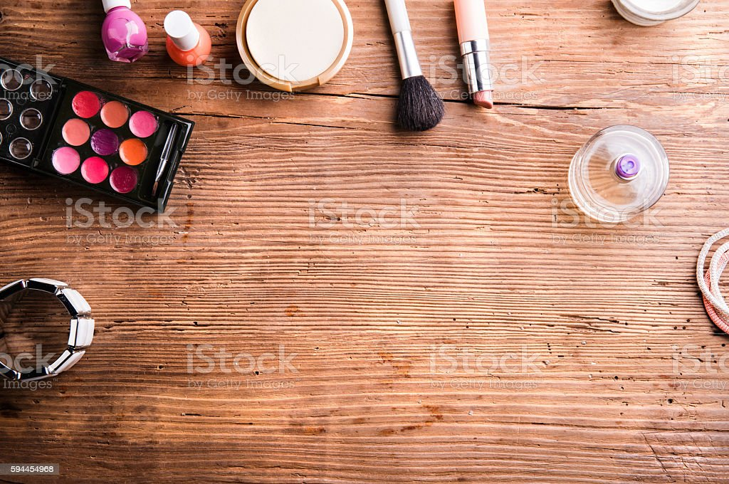 Various make up products laid on table. Studio shot on wooden...