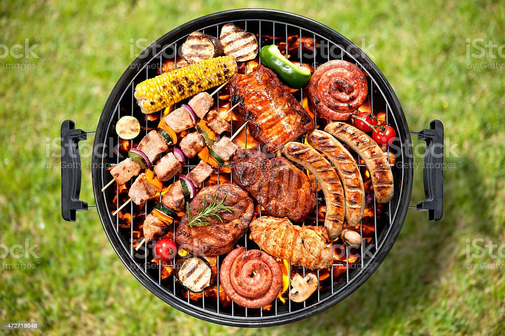 Various meats and vegetables being cooked on a grill stock photo