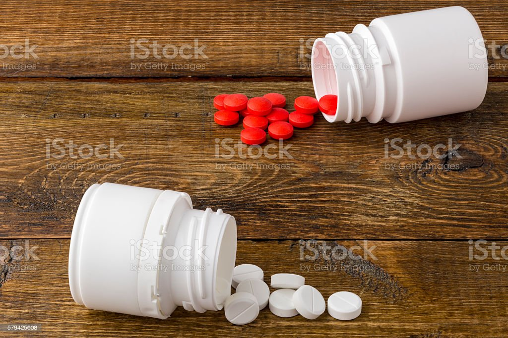 Various medical apothecary bottles with colorful pills stock photo