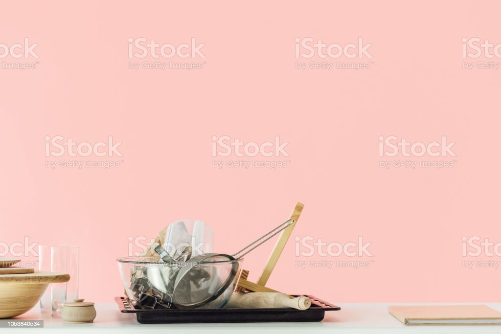 various messy cooking utensils on table isolated on pink