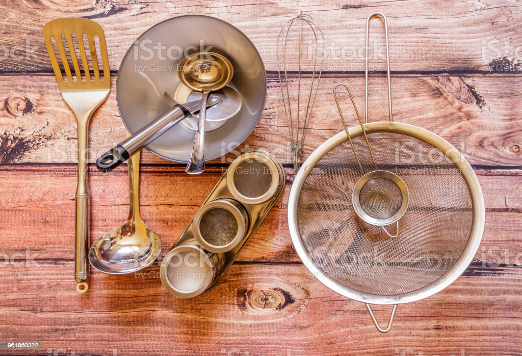 Various metal kitchen utensils on wooden background, top view royalty-free stock photo