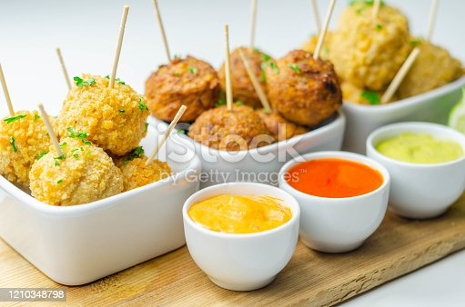 Various mini chicken kievs and sweet potato falafels served with sauces, banquet food