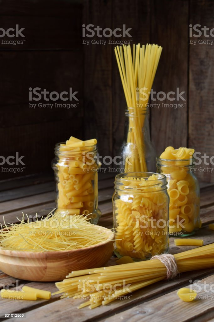 Various mix of macaroni on wooden rustic background. Assortment different kinds of Italian pasta. Diet and food concept. Spaghetti, fettuccine and tagliatelle. stock photo