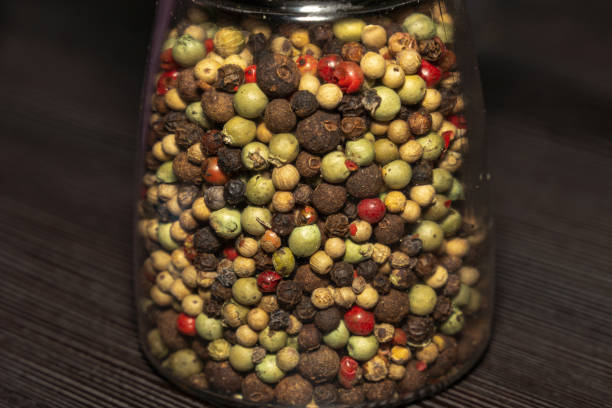 Various mixed peppercorns in a glass stock photo